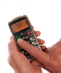 Seniorenfinger drückt Notruf auf Mobiltelefon