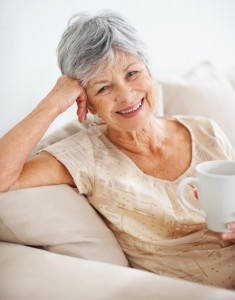 Closeup of a smiling old woman at home drinking coffee