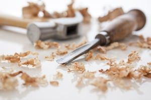 hammer and chisel on a white board with sawdust shavings